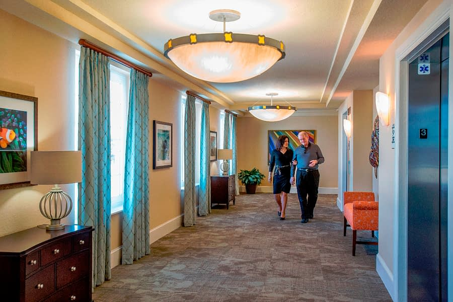 Residents walking in hallway with bench and art on the walls