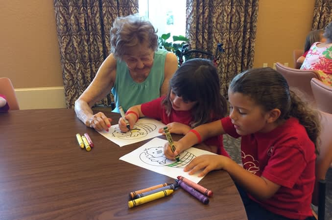 Resident helping children color during their visit
